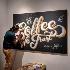 mural tipografi in coffee we trust